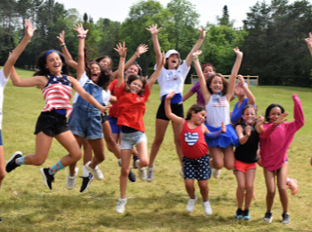 Large group of girls jumping in the air, as they celebrate the Fourth of July