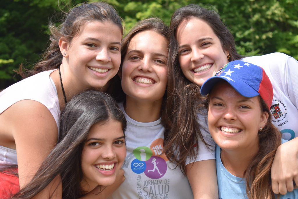 Five young girls smiling and cuddled together at overnight summer camp