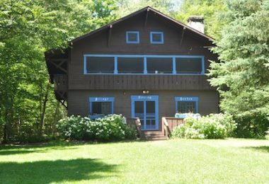 External view of a dark brown cabin with blue trim around the windows, nestled between green trees