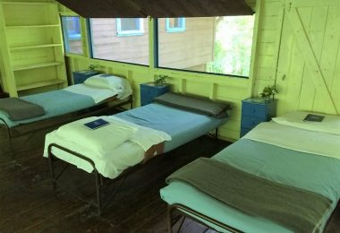 Beds and small blue nightstands, lined up and neatly made for upcoming campers to sleep in the Eagle Cabin