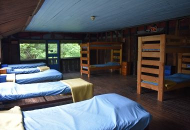 Single beds and bunk beds, perpendicular to each other, used in overnight summer camps for high school students
