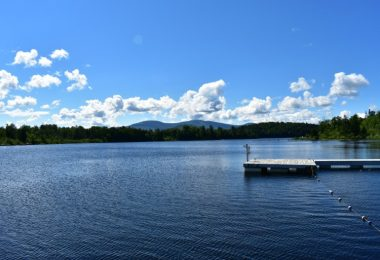 Profile of Lake Chateaugay dock, waterfront, with mountains and blue skies in the background