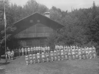 Historic flashback of the Woodsheart building, with girls gathered outside in a line
