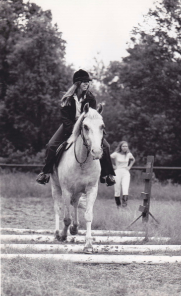 Black and white image of a young girl horseback riding