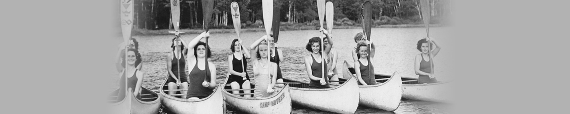 Twelve girls in canoes raising paddles vertically on the waterfront