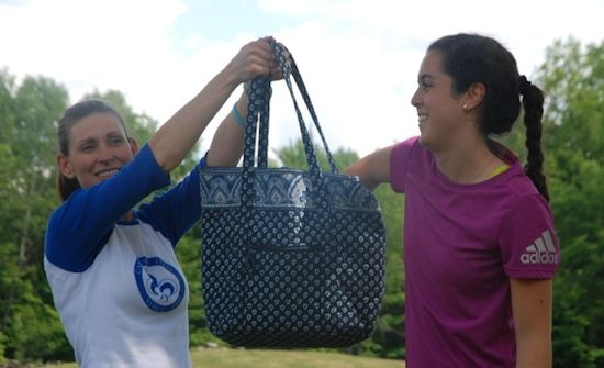 Blanca S., Camper from Spain reaching into a blue mesh bag held up by Sandy Abbott, Director of an all-girls summer camp