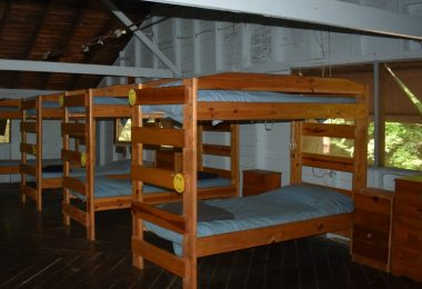 The Bluebird Cabin, featuring sets of bunk beds aligned with blue linens, next to windows