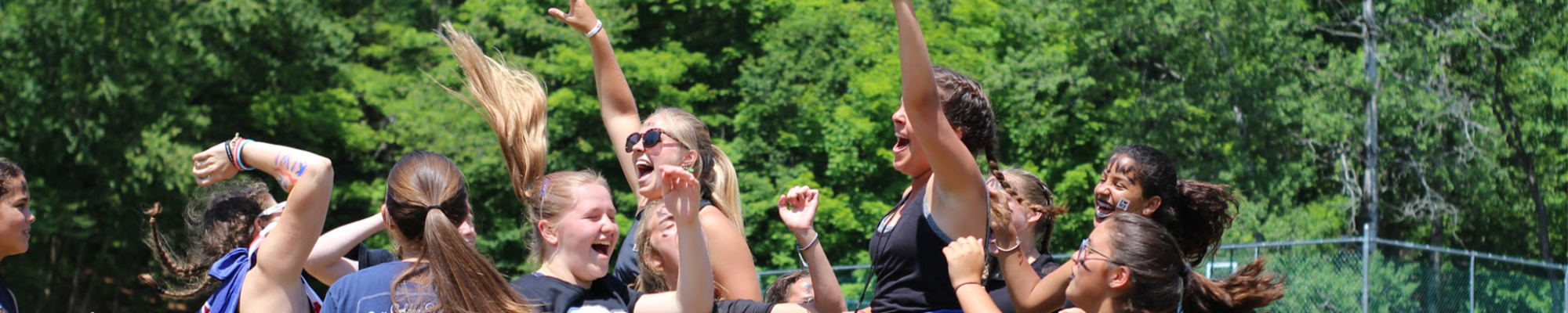 Teen girls cheering, as they attend an all-girl, affordable summer camp in New York