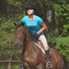 Action image of a woman in a blue shirt riding a horse