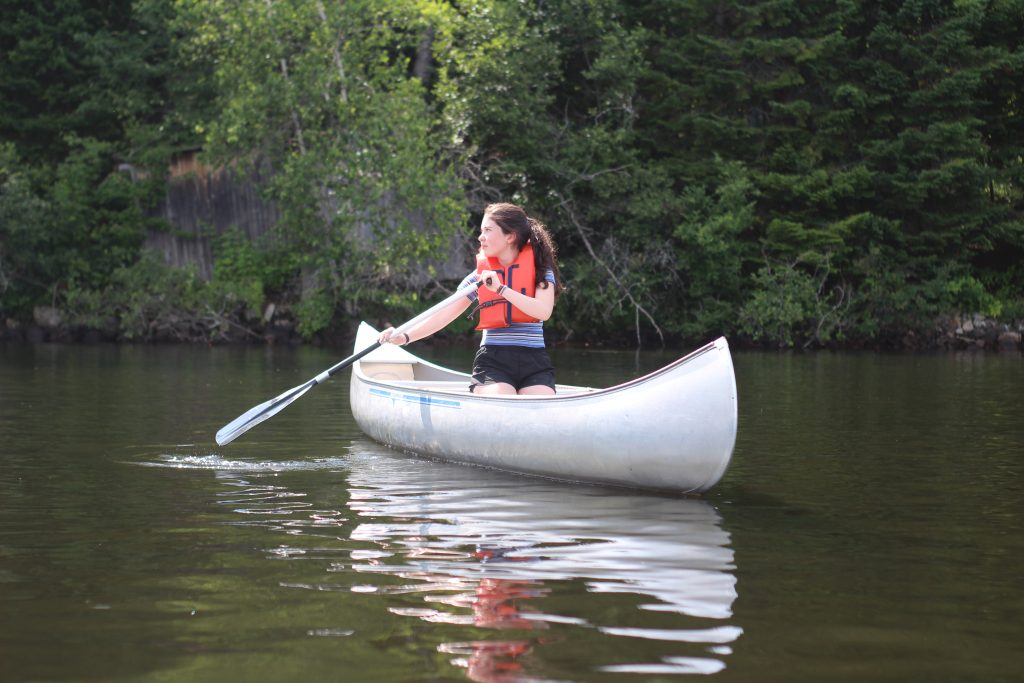 Middle-school aged female learning how to canoe, independently
