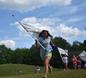 Camp counselor running with a white flag at an affordable sleep away camp