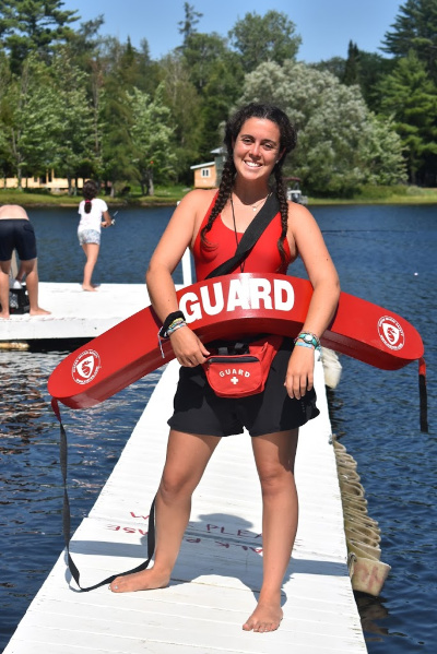 Lifeguard standing on the dock with floatation device in hand
