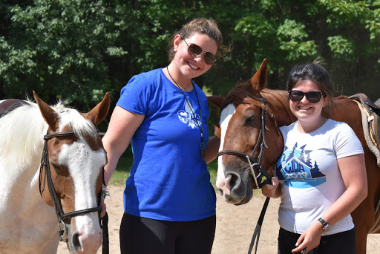 Two young people leading horses in CJDA branded t-shirts