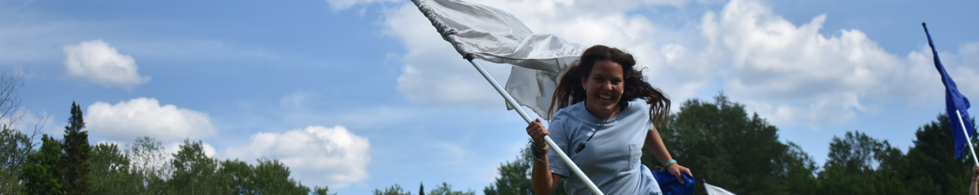 Camp counselor running with a white flag at an affordable sleepaway camp