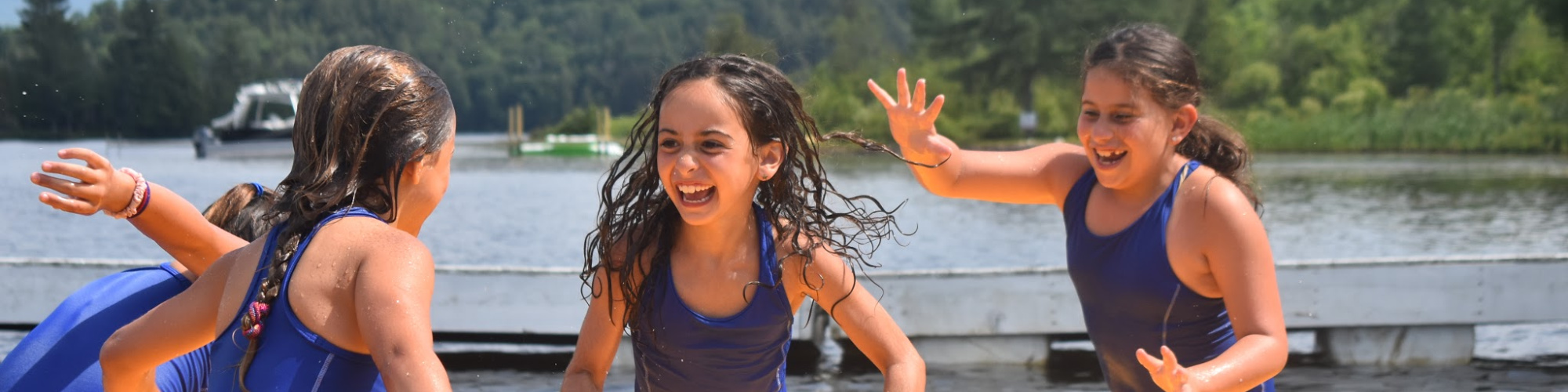 Three girls playing at the waterfront at one of the best overnight summer camps in NY