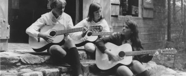 Three girls playing guitars on the steps of a Camp cabin