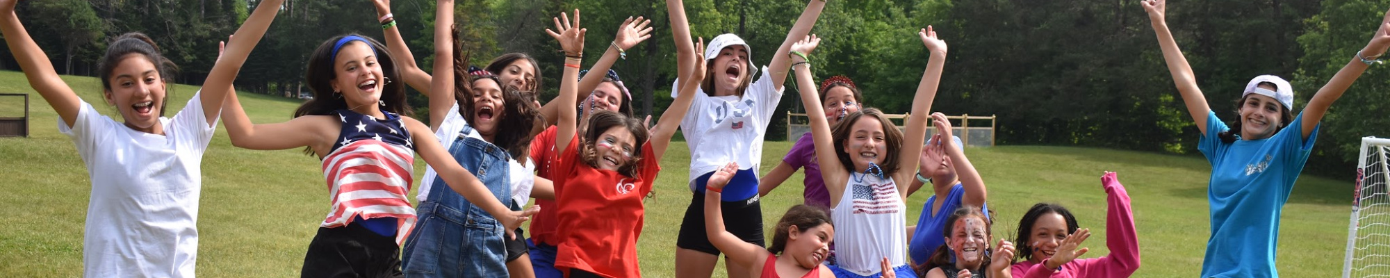 Group of girls enjoying summer camp, expressing excitement by jumping simultaneously