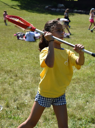 Young girl dressed in yellow shirt and blue/white buffalo check shorts playing