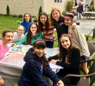Nine teens gathered together around a table, working on arts and crafts