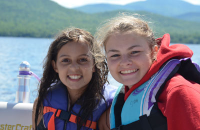 Two young friends, in lifejackets near a body of water