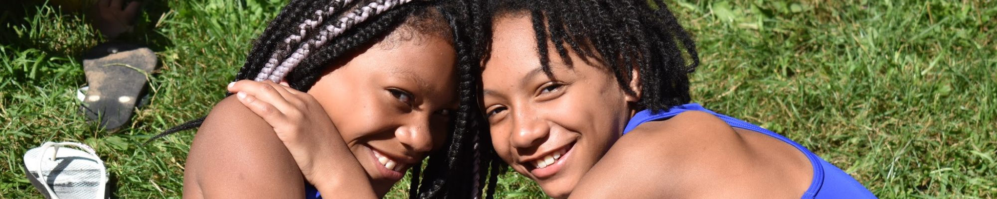Two young girls with foreheads together, looking at the camera